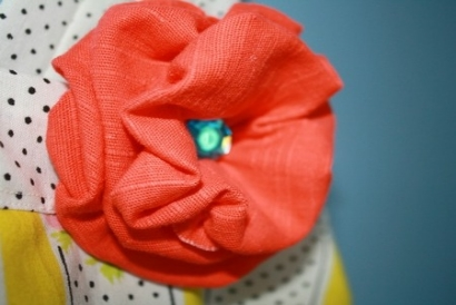 A red fabric flower with a blue gem at the center