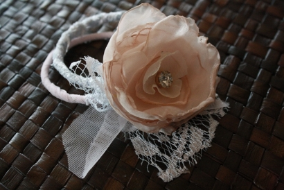 A peach colored fabric flower on a bracelet