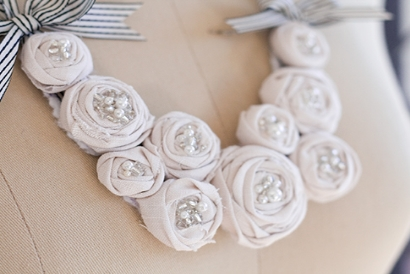 A necklace made of white fabric rosettes